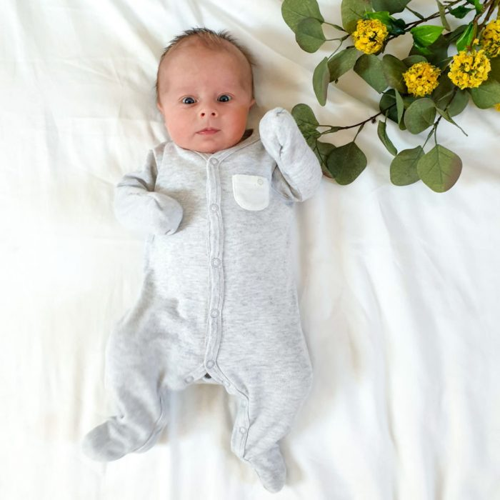 Baby laying on bed wearing sustainable organic cotton sleek-suit from Baby Mori