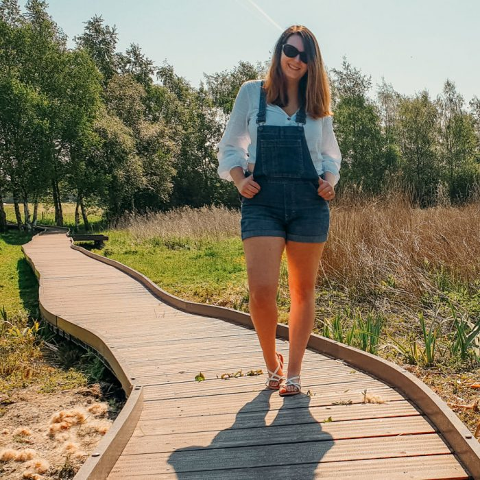 Breastfeeding mum outfit with dungarees and blouse on a boardwalk